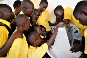 UGANDA, 2011. Young Ugandans gather around to use UNICEF's unique innovation the solar-powered Digital Drum, at Bosco Youth Centre in Gulu, Uganda. The Digital Drum was this month chosen as one of Time Magazine's Best Inventions of 2011. © UNICEF/UGDA2011-00099/YANNICK TYLLE
